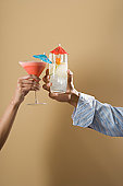 Couple toasting mixed drinks, close up of hands studio shot