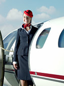 Flight attendant standing in door of private plan, portrait